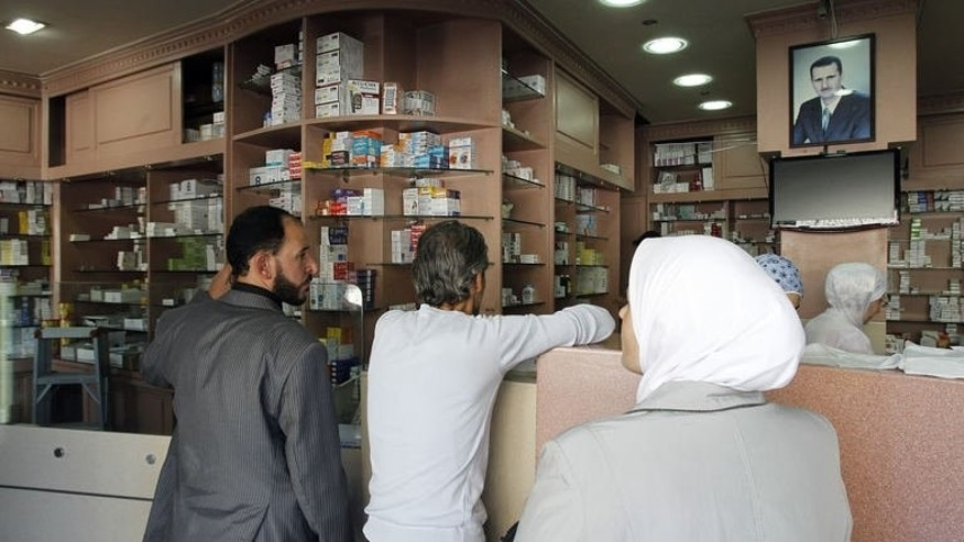 Customers queue up for medication at a pharmacy in Damascus on September 17, 2013.