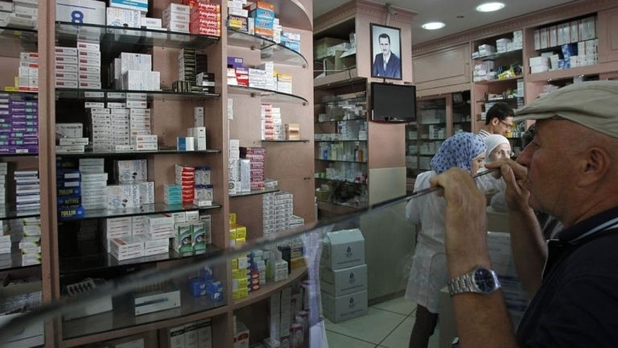 A customer waits for medication at a pharmacy in Damascus on September 17, 2013.