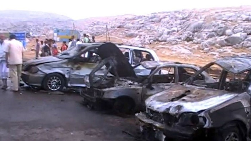 An image grab taken from a video uploaded to YouTube on September 17, 2013 shows men inspecting the alleged site of a car bomb at the main entrance to Syria's rebel-held Bab al-Hawa border crossing.