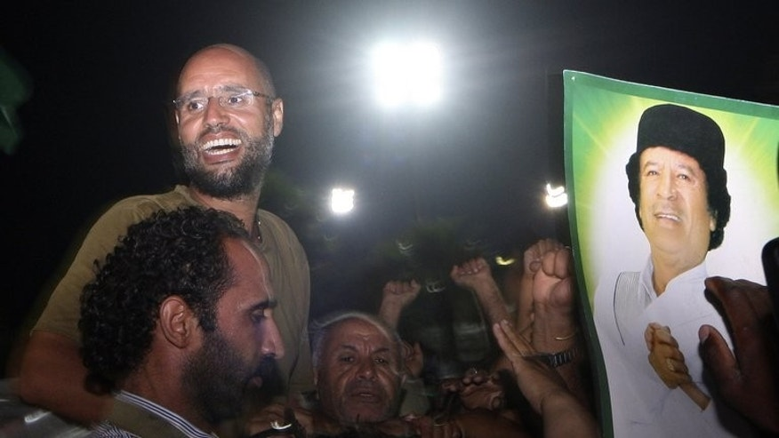 Saif al-Islam Kadhafi, son of Libyan leader Moamer Kadhafi, is surrounded by supporters at his father's residential complex in Tripoli in the early hours of August 23, 2011.