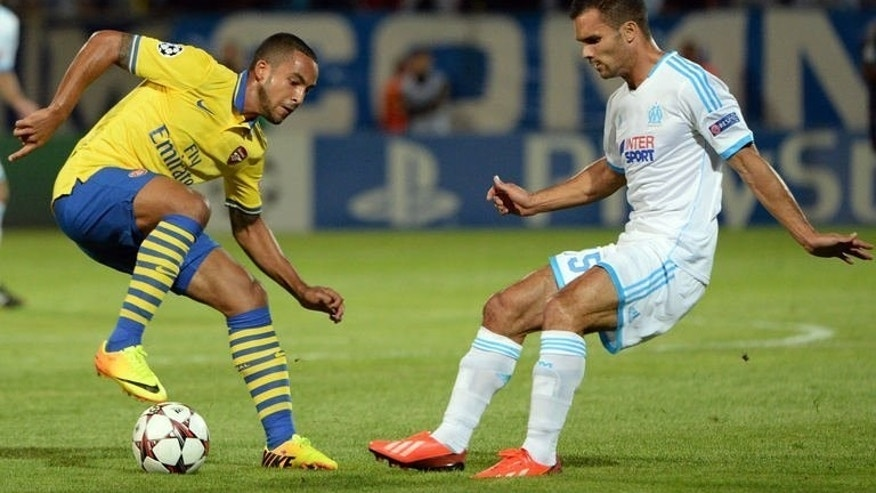 Arsenal's English midfielder Theo Walcott (L) vies with Marseille's French defender Jeremy Morel (R) on September 18, 2013 at the Velodrome stadium in Marseille, southern France, during the UEFA Champions League group F football match Marseille vs. Arsenal. Arsenal won 2-1.