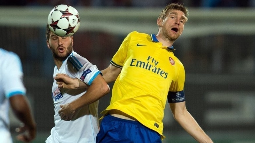 Arsenal's German defender Per Mertesacker (R) vies with Marseille's French forward Andre-Pierre Gignac during the UEFA Champions League group F football match between Marseille and Arsenal on September 18, 2013, at the Velodrome stadium in Marseille, southern France. Arsenal won 2-1.