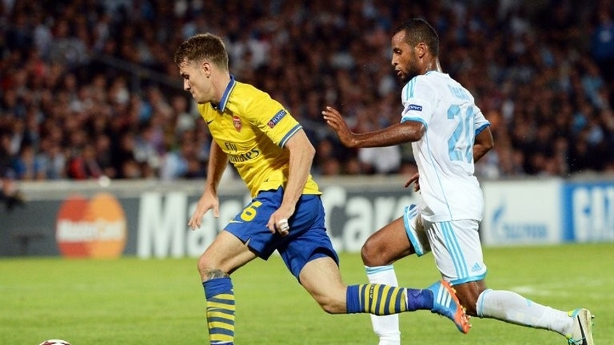 Arsenal's Aaron Ramsey (L) outpaces Marseille's Jacques-Alaixys Romao before scoring a goal on September 18, 2013 at the Velodrome stadium in Marseille, southern France, during Arsenal's 2-1 win in a UEFA Champions League group F match