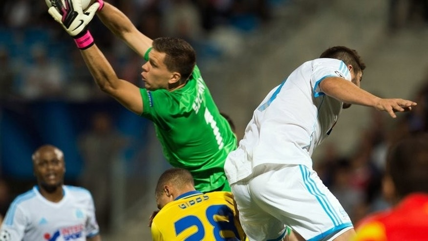 Arsenal goalkeeper Wojciech Szczesny makes a save in front of Marseille's Andre-Pierre Gignac (R) during Arsenal's 2-1 win in a UEFA Champions League group F match on September 18, 2013 at the Velodrome stadium in Marseille, southern France.