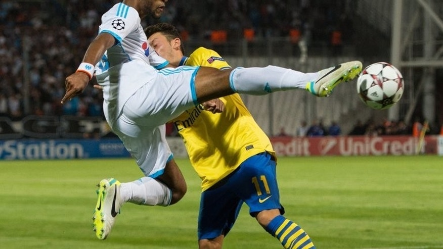Marseille's Jacques-Alaixys Romao makes an acrobatic interception in front of Arsenal's Mesut Ozil during Arsenal's 2-1 win in a UEFA Champions League group F match on September 18, 2013 at the Velodrome stadium in Marseille, southern France.