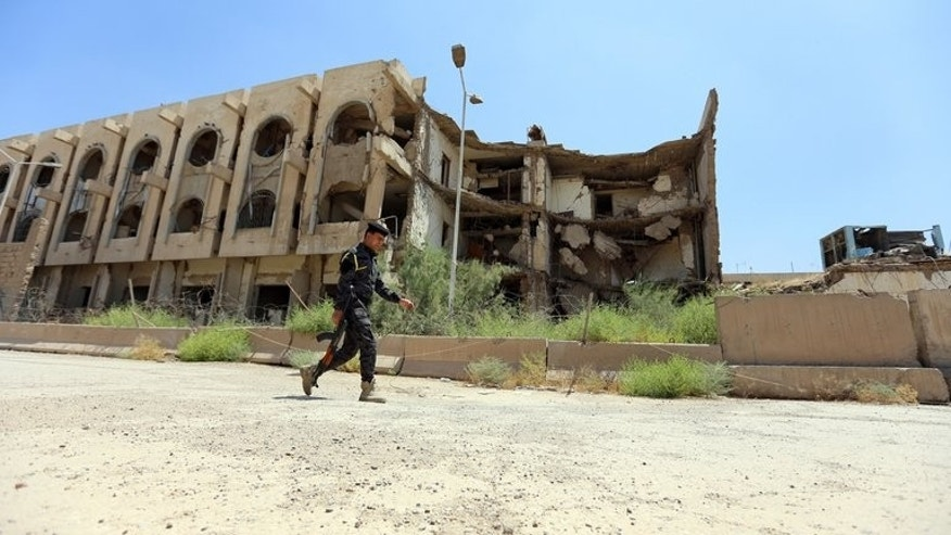 A security officer passes the destroyed former United Nations headquarters in Baghdad on August 16. The bodies of 10 young men shot in the head or chest were found on Thursday in a disused factory in the Iraqi capital, security and morgue official said.