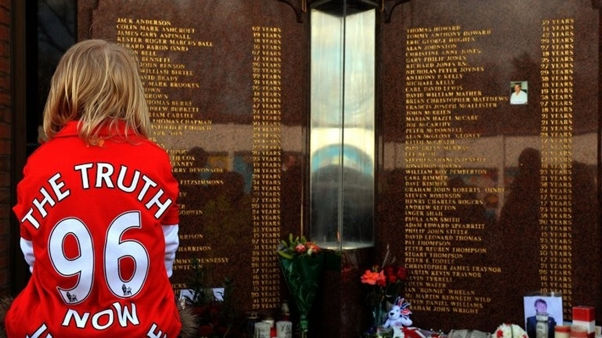 A child looks at the Hillsborough Memorial at Liverpool FC's Anfield football ground on April 15, 2013.
