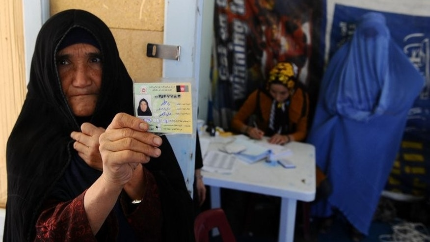 An elderly Afghan woman displays her identification card to vote in forthcoming elections at a registration centre in Herat on September 19, 2013. The newly appointed Afghan watchdog responsible for investigating fraud in the 2014 presidential election vowed on Thursday to ensure a fair vote despite accusations over its independence.