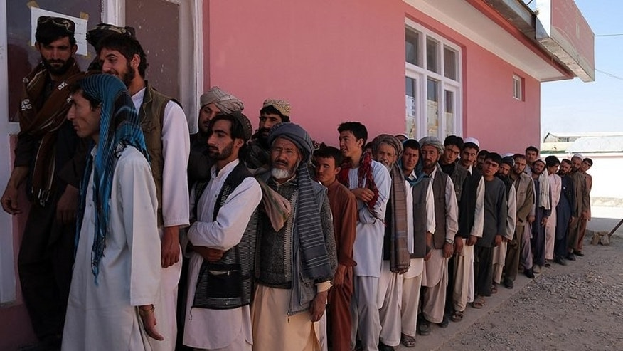 Afghan men wait to receive their identification cards to vote in upcoming elections at a registration centre in Ghazni on September 17, 2013. The newly appointed Afghan watchdog responsible for investigating fraud in the 2014 presidential election vowed on Thursday to ensure a fair vote despite accusations over its independence.