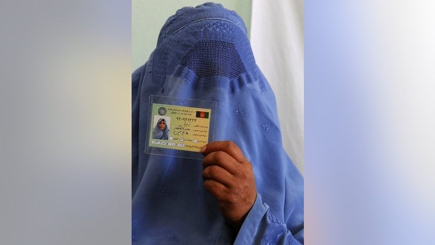An Afghan woman displays her identification card to vote in forthcoming elections at a registration centre in Herat on September 19, 2013. The newly appointed Afghan watchdog responsible for investigating fraud in the 2014 presidential election vowed on Thursday to ensure a fair vote despite accusations over its independence.