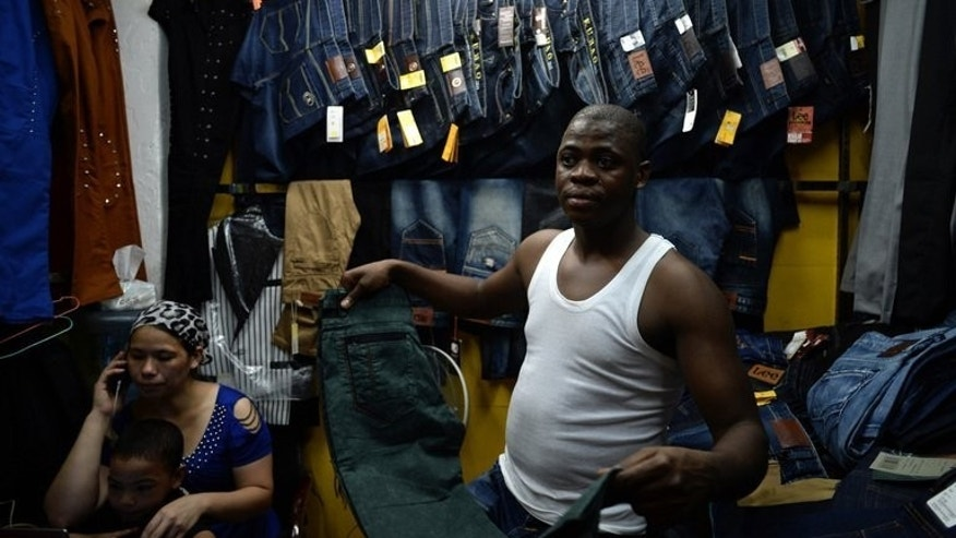 Lamine Ibrahim and his wife and child are pictured inside their shop at a clothing wholesale market in Guangzhou on August 26, 2013. Guangdong, a mecca for low-cost manufacturing, has drawn entrepreneurs from across Africa, creating one of the largest black communities in Asia.