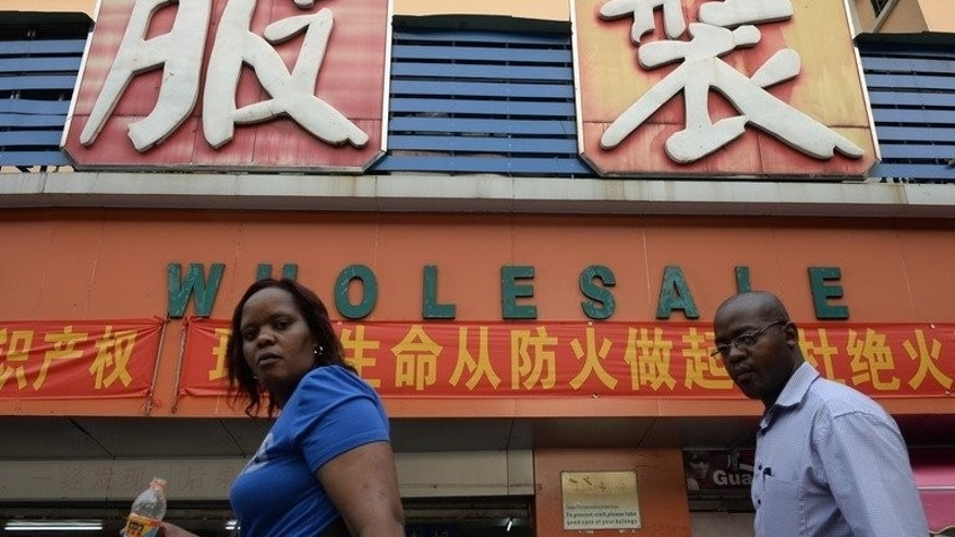 An African man and woman walk past a clothing wholesale market in Guangzhou on August 26, 2013. The low-cost manufacturing mecca of Guangdong draws entrepreneurs from across Africa, creating one of the largest black communities in Asia.