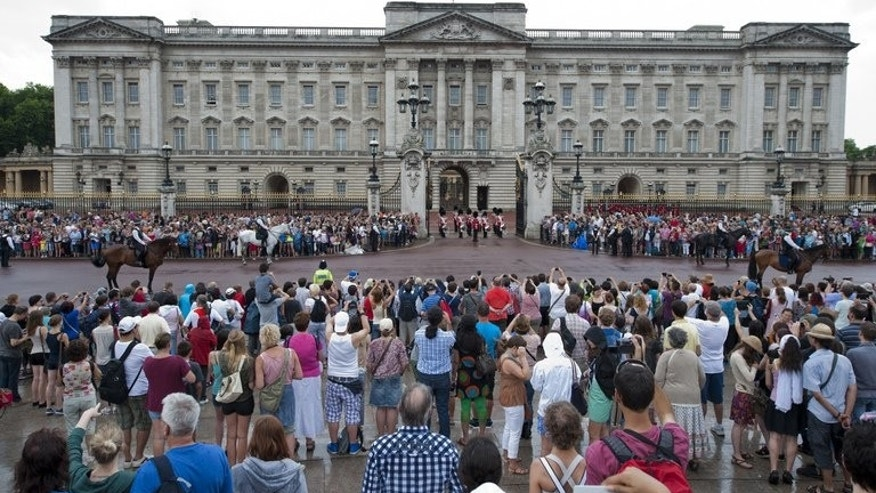 Crowds gather outside Buckingham Palace on July 23, 2013. Preparations for the first football match to be staged at th palace were stepped up when a pitch was marked out in the garden.
