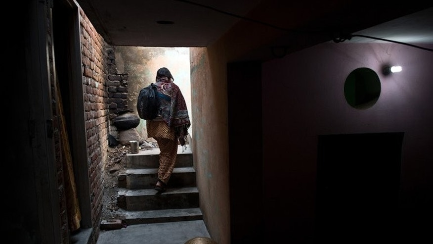 "A woman walks up stairs in Haryana state, India, on January 23, 2013. A man was beheaded and his girlfriend beaten to death in an ""honour killing"" in northern India after they eloped, police said Thursday."