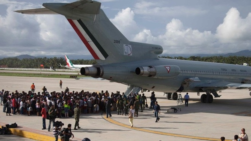 Sept. 17, 2013: Hundreds of stranded tourists gather around a Mexican Air Force jet as they wait to be evacuated, at the air base in Pie de la Cuesta, near Acapulco, Mexico.