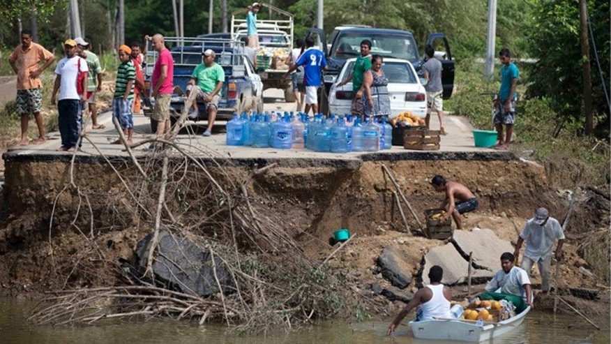 Sept. 18, 2013: People stand on the edge of a collapsed bridge as they wait to ferry their goods via a boat across the Papagayos River, south of Acapulco, near Lomas de Chapultepec, Mexico.