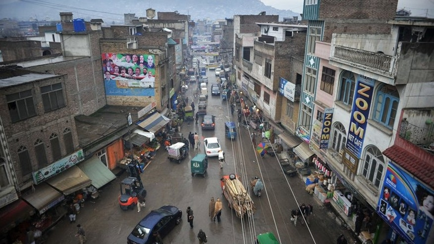 Pakistani pedestrians and cars travel down a street in Mingora, the main town in the Swat Valley, on January 12, 2013. Authorities in Pakistan's northwestern Swat Valley have declared a health emergency after nearly 5,000 cases of dengue fever were reported in a month.