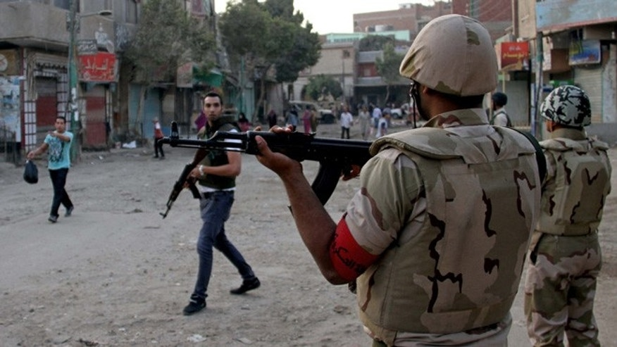Sept. 19, 2013: Egyptian security forces hold their weapons during clashes with suspected militants, not pictured, in the town of Kerdasa, near Giza Pyramids, Egypt. Egyptian security forces backed by armored vehicles and military helicopters on Thursday laid a siege on an Islamists stronghold near Giza Pyramids and exchanged fire with what official news agency identified as terrorist and criminal elements.