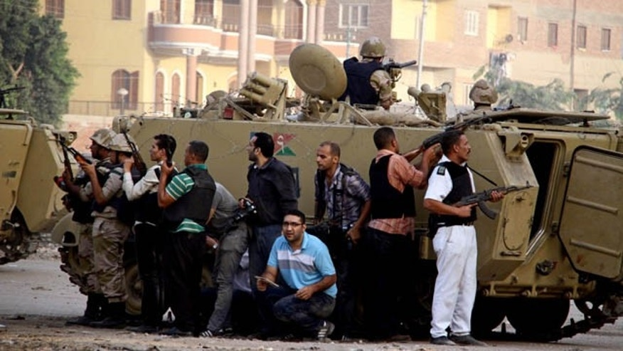 "September 19, 2013: Egyptian security forces take cover during clashes with suspected militants, not pictured, in the town of Kirdasah, near Giza Pyramids, Egypt. Security forces backed by armored vehicles and military helicopters on Thursday laid a siege and exchanged fire with what official news agency identified as ""terrorist and criminal elements."" (AP Photo)"