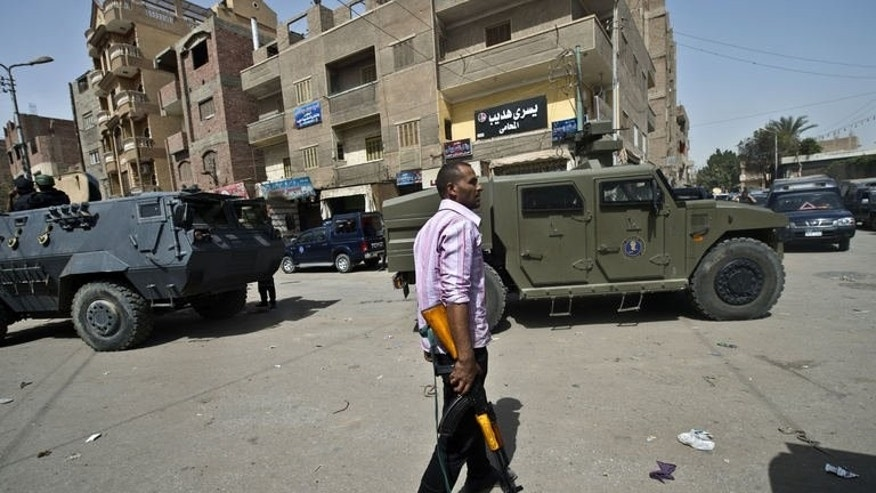 An Egyptian armed policeman holds a position in a street during a raid in the village of Kerdassah on the outskirts of Cairo, on September 19, 2013.