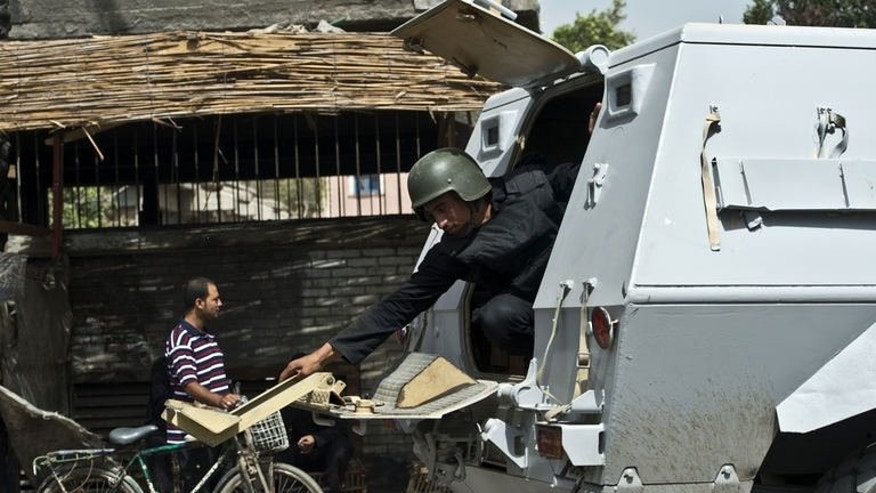 An Egyptian armed policeman closes the door of an armored vehicle during a raid in the village of Kerdassah on the outskirts of Cairo, on September 19, 2013.