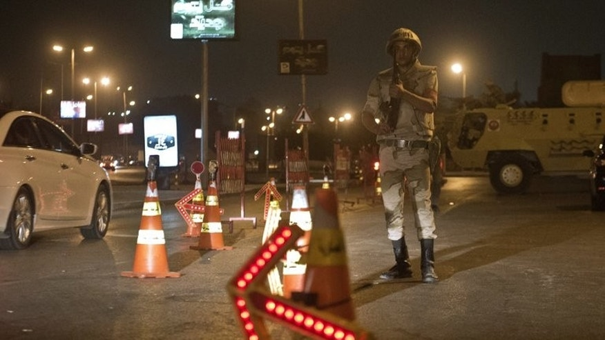 Troops keep watch at a checkpoint during the curfew hours in Cairo late on August 19. Egypt is to shorten a night-time curfew imposed on Cairo and 13 provinces starting Saturday, the cabinet said on Thursday.