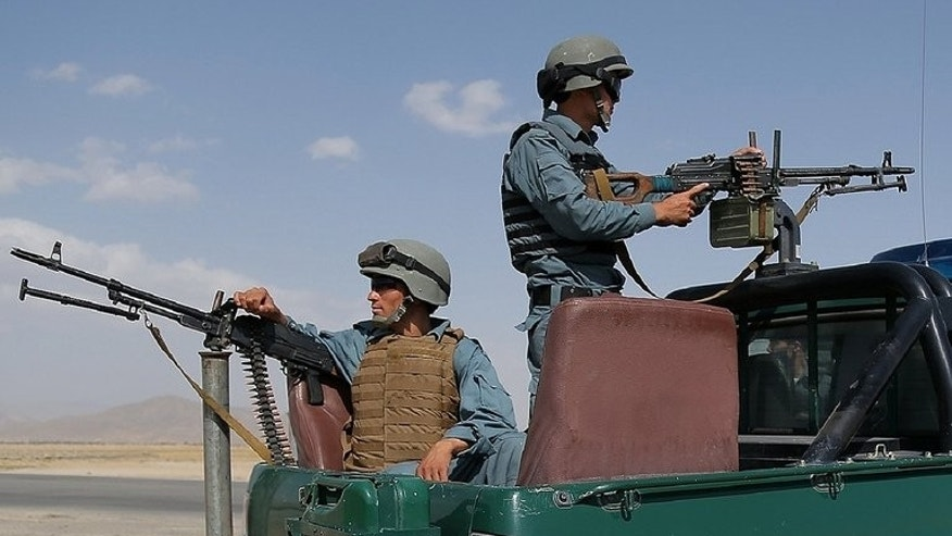 Afghan policemen keep watch at a checkpoint in Ghazni on August 14, 2013. A former Afghan lawmaker and district governor said Thursday he had defected to the Taliban as the Islamist hardliners seek to strengthen their influence before US-led combat troops withdraw next year.