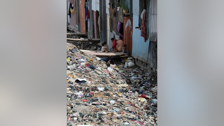 An Indian mother sits with her children outside their slum home strewn with garbage in Mumbai on June 4, 2013.