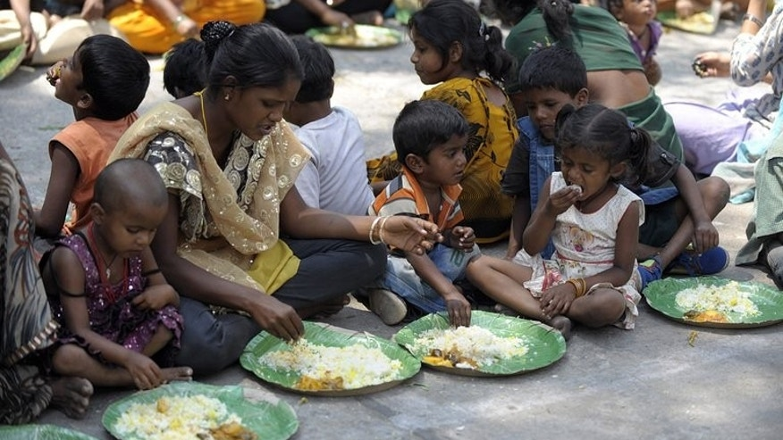 File photo shows Indian homeless eating food at a feeding programme for the poor in Hyderabad.