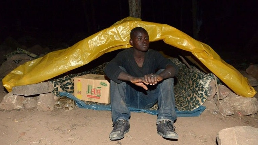 An African migrant sits in a tent as he hides in a forest in the eastern coastal city of Nador on September 18, 2013. In a forest overlooking the Spanish enclave of Melilla, Diamani nurses fresh wounds from his latest desperate bid, along with hundreds of other African migrants, to scale the heavily guarded border fence.