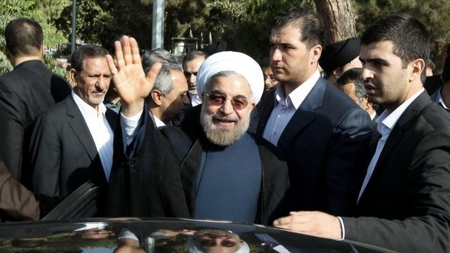 Hassan Rowhani waves after visiting the tomb of Ayatollah Ruhollah Khomeini in the south of Tehran on August 24. Iran's new president appears to be keeping campaign pledges of broader domestic freedoms, a week before heading for New York as he seeks to rebuild Iran's tarnished international image.