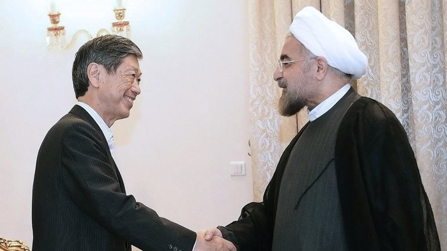 "Hassan Rowhani (right) greets Japanese envoy Masahiko Komura in Tehran on September 8. Rowhani has pledged that Tehran will never seek to acquire atomic weapons while insisting there was ""sufficient political latitude"" in Iran to resolve the nuclear showdown."