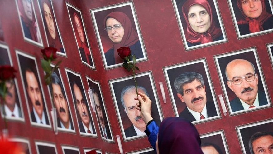 Maryam Radjavi places roses beside the portraits of victims at a ceremony to honor 52 persons killed in the Ashraf refugee camp, on September 6, 2013 in Auvers-sur-Oise, outside of Paris.