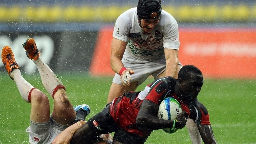 England players tackle Kenya's Humphrey Kayange at the 2013 Rugby World Cup Sevens Championships in Moscow in June. The Safaricom Sevens gets underway in Nairobi on Friday.