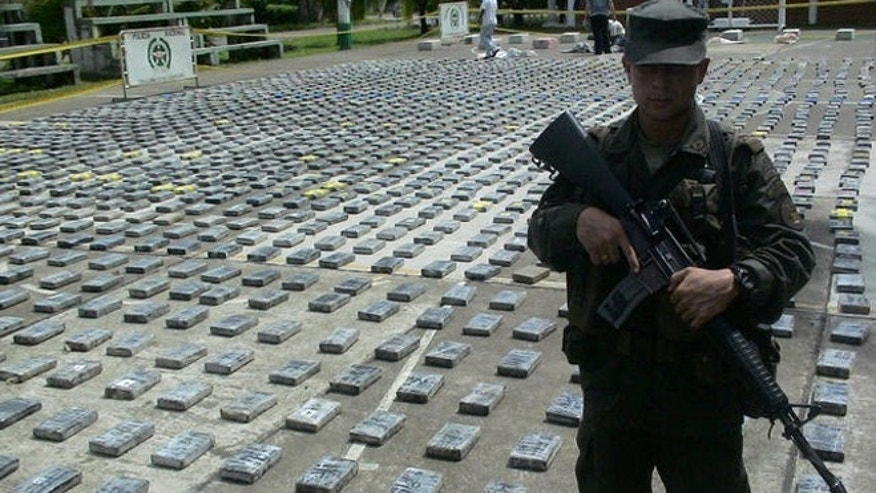 Anti-narcotics police officer  guards packages of cocaine, totaling  2.9 tons, seized during a raid at a lab in the rural area of Necocli, in the norther Colombian Caribe coast,  Colombia on Monday, June 26, 2006.. (AP Photo/Luis  Benavides)