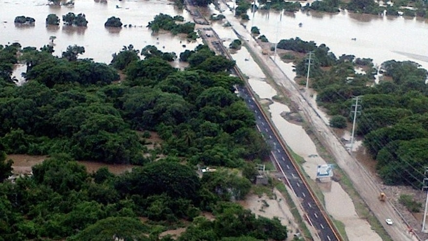 An aerial view of flooding along the highway going to Acapulco, in the Mexican state of Guerrero, as heavy rains hit the country, in a photo taken and released on September 18, 2013 by Mexico's Interior Ministry. A rumbling noise came from the hill before the earth crashed down on the Mexican hamlet of La Pintada, burying people, the school and church after days of rain, survivors told AFP.