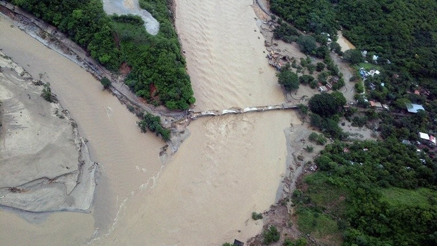 An aerial view of a damaged bridge along the highway going to Acapulco, in the Mexican state of Guerrero, as heavy rains hit the country on September 18, 2013, in a photo from Mexico's Interior Ministry. A rumbling noise came from the hill before the earth crashed down on the Mexican hamlet of La Pintada, burying people, the school and church after days of rain, survivors told AFP.