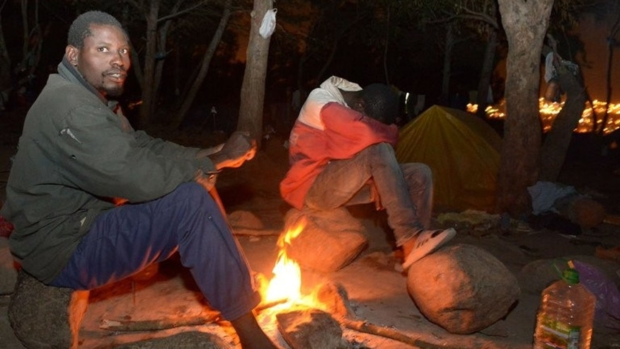 African migrants sit near a fire as they hide in a forest in the eastern coastal city of Nador on September 18, 2013. African migrants charged a barbed-wire border fence and tried to enter the Spanish exclave of Melilla from Morocco, local officials said, the latest in a string of coordinated assaults on the frontier.