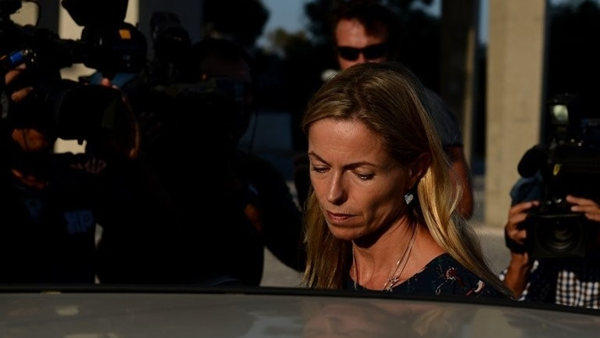 Kate McCann, mother of missing British girl Madeleine McCann, is mobbed by reporters as she leaves the court house in Lisbon on September 12, 2013.
