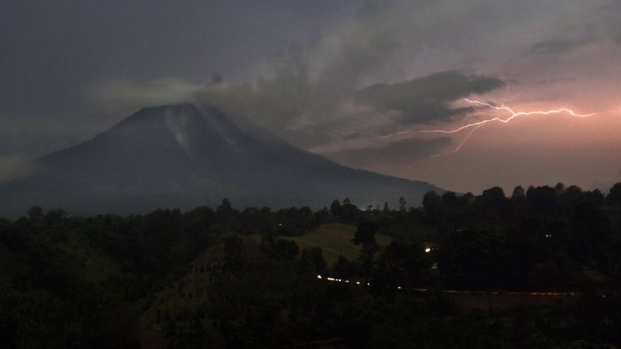 Lightning strikes next to Mount Sinabung volcano as it spews steam and ash on September 18, 2013. More than 15,000 people have now fled their homes since Mount Sinabung in western Indonesia spectacularly erupted this week, an official said Thursday.