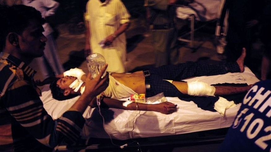 Pakistani men carry injured victims to a hospital after a grenade attack in Karachi on September 19, 2013.