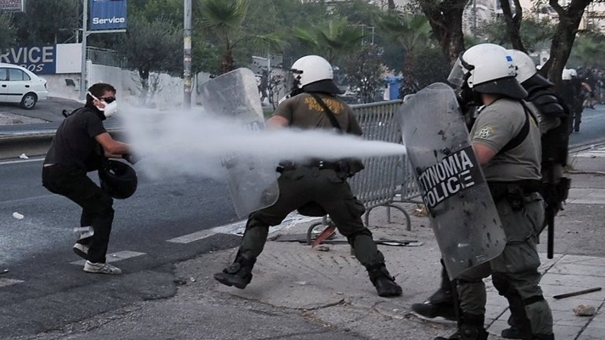 Police spray a protester with tear gas during clashes with anti-fascist demonstrators in the western Athens working class suburb of Keratsini on September 18, 2013. The Greek press railed on Thursday over the murder of a leftist musician by an alleged supporter of the neo-Nazi party Golden Dawn, amid mounting calls for tighter control of the group.