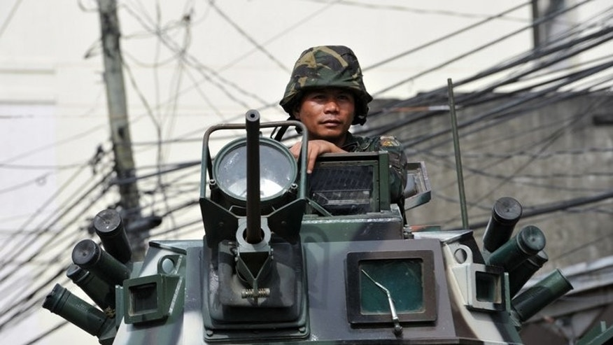 A soldier on board an armoured personnel carrier arrives at the site of a standoff with remnants of Muslim rebels in the city of Zamboanga in the Philippines on September 19, 2013. Philippine security forces killed eight Muslim rebels Thursday as they hunted the remnants of a guerrilla force hiding in homes of a major city and believed to be holding hostages.