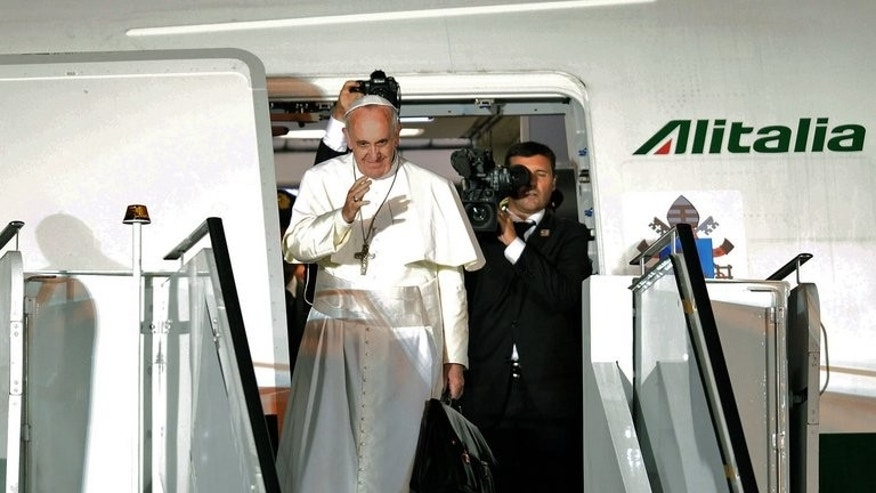 "Pope Francis waves as he boards the plane after a week-long trip to Brazil, on July 28, 2013. Pope Francis on Thursday lashed out at what he called the scandal of ""airport bishops"", urging his peers to remain rooted in their dioceses and spend less time seeking the spotlight."