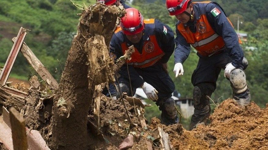 Mexican Federal Police search for bodies on the site of a landslide in La Pintada, Guerrero state, on September 19, 2013 as dozens remain missing