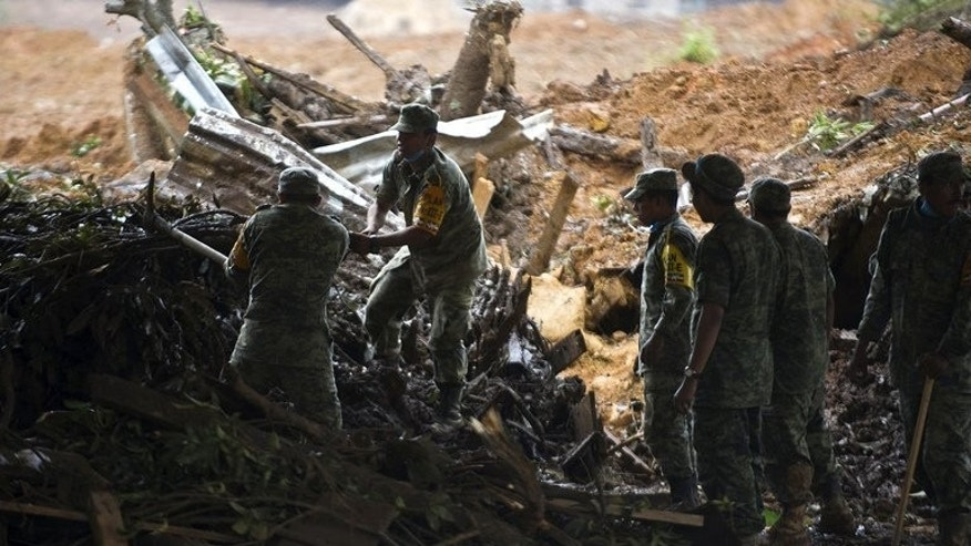 Mexican soldiers search through debris in La Pintada, Guerrero state, on September 19, 2013 after a mudslide buried the village leaving dozens missing