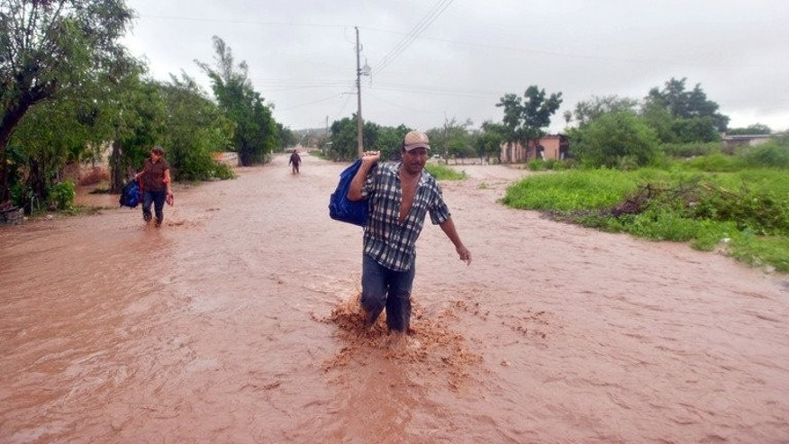 Residents of El Zapotillo evacuate their homes because of flooding in the state of Sinaloa, Mexico, on September 19, 2013, after storms lashed the country and killed almost 100 people nationwide.