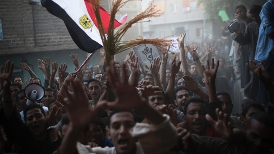 Sept. 17, 2013: In this photo, supporters of Egypt's ousted President Mohammed Morsi chant slogans against Egyptian Army during a protest in Dalga, south of Cairo, Egypt. Even after the military and police stormed Dalga to wrest it from control of Islamic militants, the town's Christians fear the protection won't last and that a worse retaliation by hard-liners is still to come.