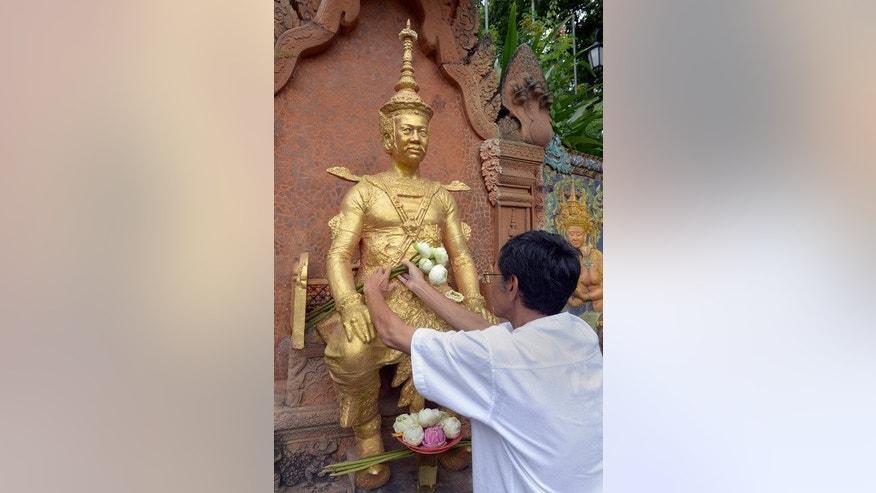 Cambodian Prince Sisowath Thomico lays flowers in front of a statue of King Sisowath during his hunger strike at Wat Phnom in Phnom Penh on September 20, 2013.