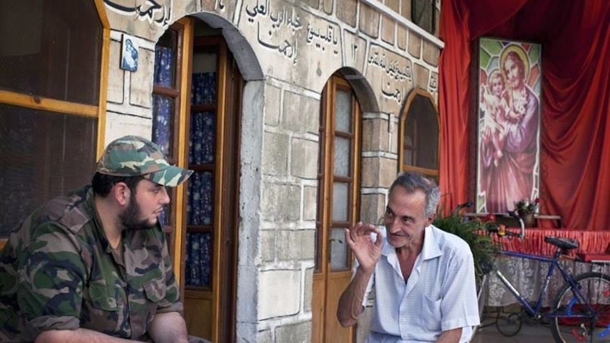 Michael Oberi, a Christian, talks with a Syrian rebel at Mar Elias House in Aleppo on Monday. As social media abound with horror stories of jihadists murdering minorities in Syria, a group of elderly Christians in Aleppo and the rebels who care for them portray a different reality.